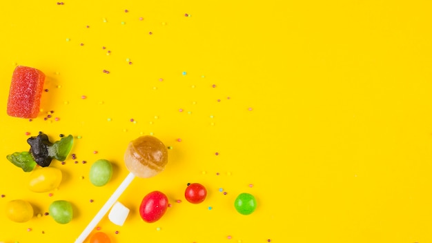 Vivid colorful candies on yellow background