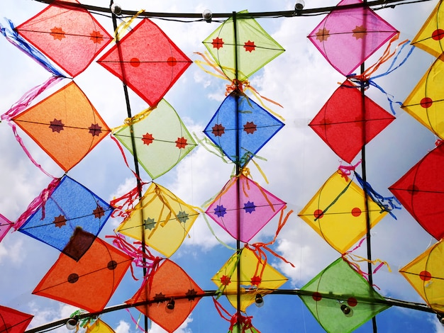 Vivid colorful decorative kites against cloudy sky
