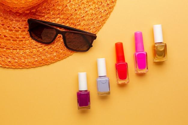Яркие цветные вариации лака для ногтей на оранжевом фоне с солнцезащитными очками и шляпой