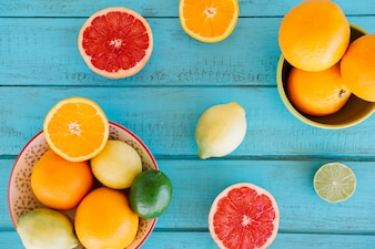 Vivid fresh citrus fruits on wooden surface