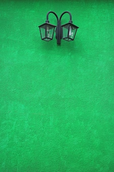 Vivid green colored concrete wall with a pair of retro street lamp, el calafate, argentina