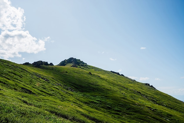 Vivid green hill with rock on top under blue sky with clouds.