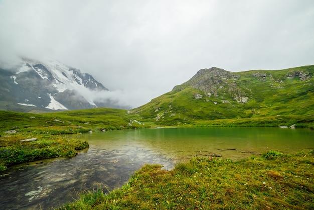 낮은 구름 사이 산 호수에 빗방울이 생생한 녹색 풍경.