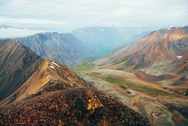 Яркий многоцветный пейзаж зеленой долины среди больших скалистых гор.