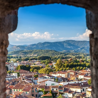 Vivid rooftops of city lucca with background of colorful green mountains range, italy.