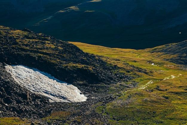 日光の下で緑の山の谷の丘の中腹に小さな氷河のある鮮やかな風景