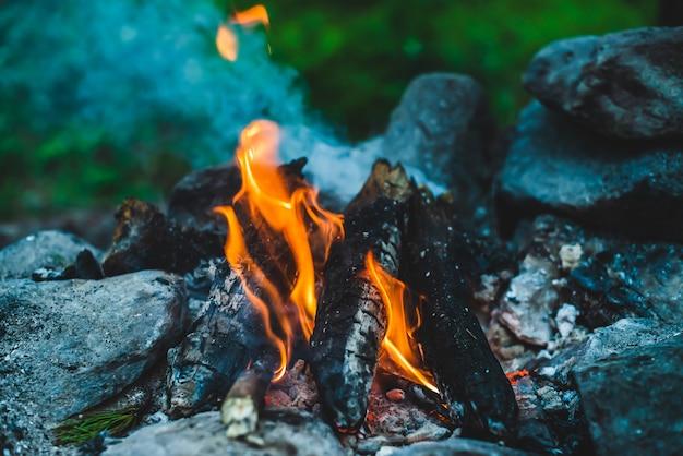 鮮やかなくすぶった薪が火のクローズアップで燃やされました。キャンプファイヤーのオレンジ色の炎と青い煙で暖かい雰囲気。たき火の想像を絶するフルフレーム画像。美しい火の中で燃えている丸太。