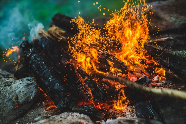 鮮やかなくすぶった薪が火のクローズアップで燃やされました。キャンプファイヤーのオレンジ色の炎と青い煙のある雰囲気。たき火の暖かいフルフレーム画像。空気中の輝く残り火。ボケ味の明るい火花