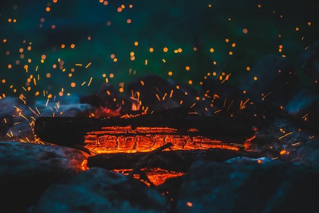 鮮やかなくすぶった薪が火のクローズアップで燃やされました。キャンプファイヤーのオレンジ色の炎のある雰囲気。空気中の輝く残り火でたき火の素晴らしいフルフレーム画像。暖かい丸太、明るい火花ボケ