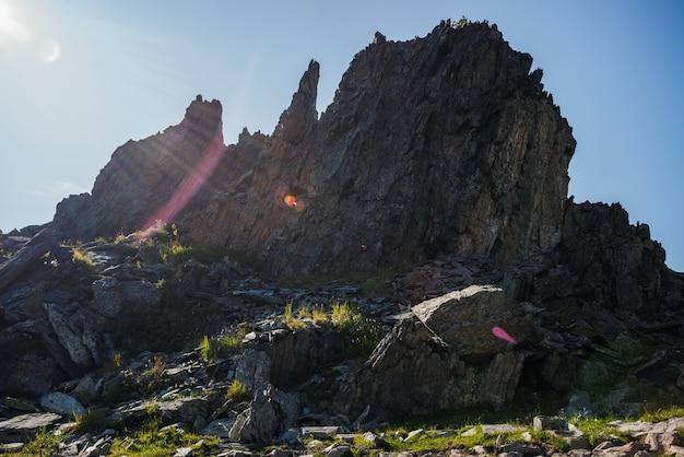 大きな鋭い岩のシルエットに鮮やかな太陽フレアと日当たりの良い梁。晴れた日の山頂の緑に囲まれたとがった石。草と日光の下で石の上の花。素晴らしい山岳風景。