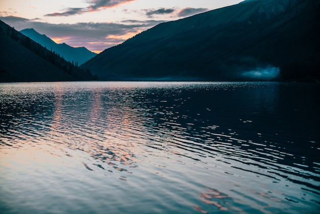 Vivid sunrise sky is reflected in pure alpine lake near mountain silhouettes. colorful scenery with calm water of mountain lake in dawn colors. beautiful landscape with water ripple in sunny morning.