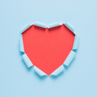 Vivid torn paper heart on bright background.