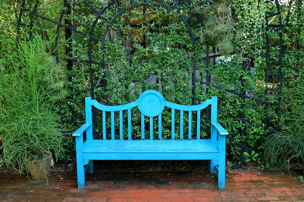 Vivid turquoise blue colored wooden bench on the terracotta brick pathway in green garden