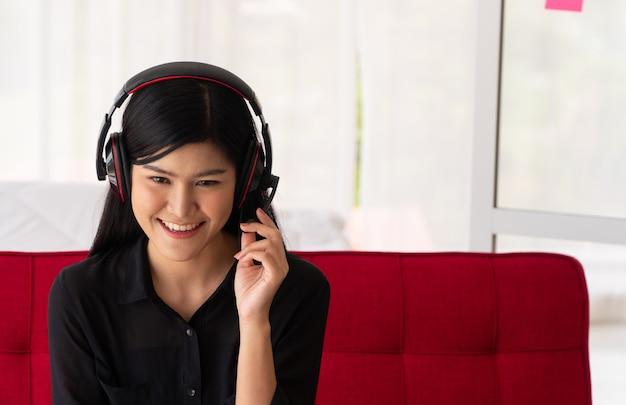 Видеоблог азиатская женщина-блогер, влиятельная женщина, сидящая на диване дома и записывающая видеоблог для обучения и наставничества своих учеников или подписчика. концепция создателя контента онлайн для нового образа жизни