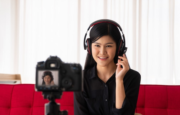 Vlog 아시아 여성 블로거 인플 루 언서가 집에서 소파에 앉아 학생들을 가르치고 코치하기 위해 비디오 블로그를 녹화합니다.