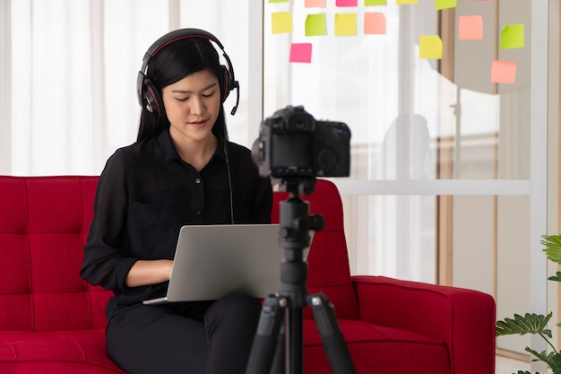 Vlog asian woman blogger influencer sitting on the sofa in home and recording video blog for teaching student