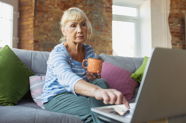Vlogブログselfie自宅で勉強している年配の女性がオンラインコースの自己開発を取得しています