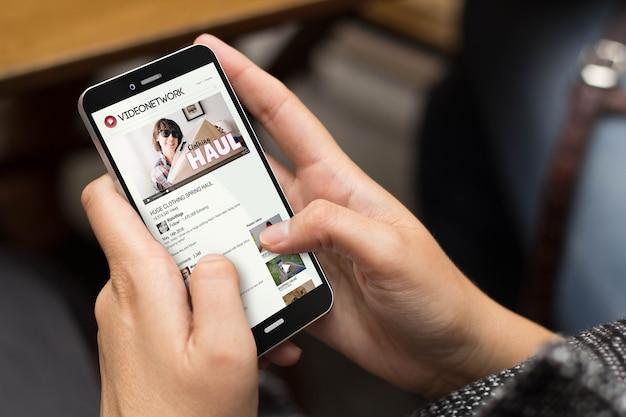 Vlogのコンセプト:画面にチューブビデオチャンネルを備えたデジタル生成された電話を使用している女の子