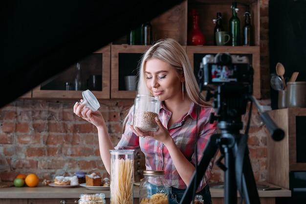 영양에 관한 vlog 에피소드. 조리. 로프트 주방 스튜디오. 백 스테이지 사진. 항아리와 금발의 젊은 여자.