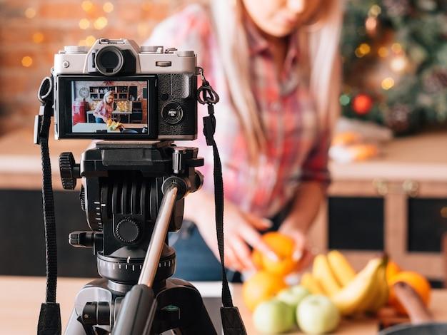 건강한 영양에 대한 블로그. 과일 구색을 가진 음식 블로거. 부엌에서 비디오를 녹화하는 젊은 여자.