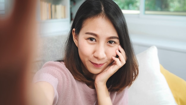 Молодая азиатская женщина подростка vlog дома, женщина используя smartphone делая видео vlog к социальным средствам массовой информации в живущей комнате. женщина образа жизни ослабляет в концепции утра дома.
