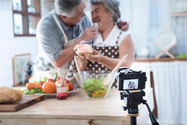 家庭の台所でカップルシニアアジア高齢者幸せな生活。祖父がソーシャルブロガーのためにジャムvlog vdoでパンを食べた後、祖母の口を拭く。