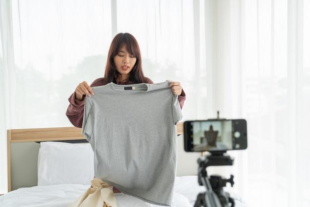 Красивый азиатский блоггер женщины показывая одежды на камере для того чтобы записать видео vlog