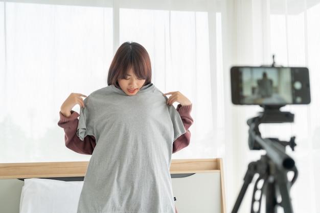 Красивый азиатский блоггер женщины показывая одежды на камере для того чтобы записать потоковое видео vlog в реальном маштабе времени в ее магазине - онлайн влияния на концепции социальных медиа