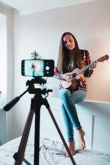 シャツとジーンズの女の子が電話でウクレレの演奏についてvlogを書いています。