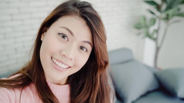 アジアのブロガーの女性が自宅の居間でvlogビデオを録画するスマートフォンを使用