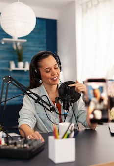 Vlogger on air during her podcast channel using mixer and professional microphone. online show production internet broadcast host streaming live video, recording digital social media communication