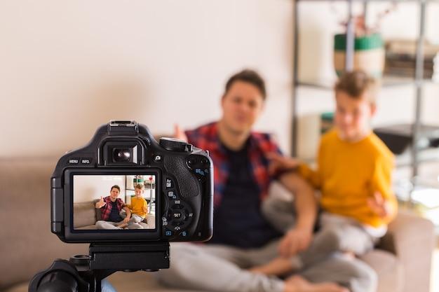 Семья vlogger записывает видео в социальных сетях, сидя на диване