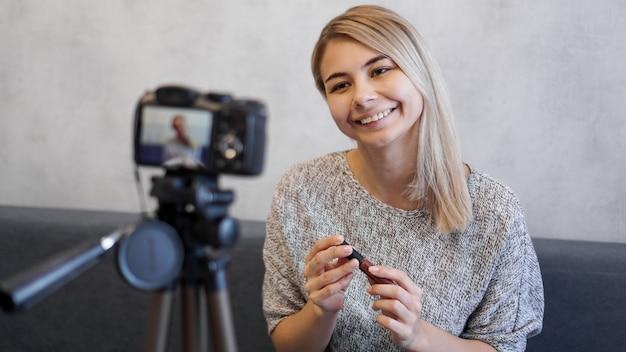 블로거 여성 보여주는 립스틱. 삼각대에 카메라 근처에서 매일 메이크업 루틴 자습서를 촬영하는 뷰티 블로거 여자