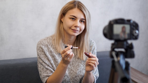 Vlogger female showing lipstick. beauty blogger woman filming daily make-up routine tutorial near camera on tripod