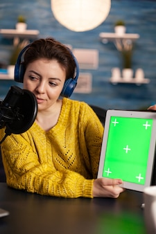 Vlogger가 노트북을 보고 크로마 키 데스크탑이 있는 태블릿에 대해 이야기하고 있습니다. 온에어 프로덕션 인터넷 방송 호스트는 mochup, 그린 스크린, izolated 데스크탑을 사용하여 라이브 콘텐츠를 스트리밍합니다.