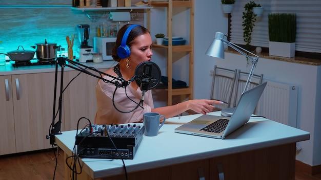Vloggerは、ソーシャルメディアのホームスタジオでポッドキャストを録音しながら、オンライン視聴者にメッセージを送信します。クリエイティブなオンラインショーオンエアプロダクションインターネット放送ホストストリーミングライブコンテンツ、レコーディングデジタル