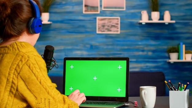 홈 스튜디오에서 라이브 스트리밍하는 동안 크로마 키 데스크톱이있는 노트북에서 vlogger 읽기