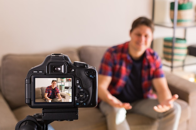 Vlogger recording social media video while sitting on the couch