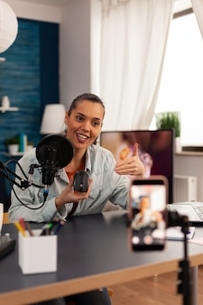 Vlogger smiling for audience and starting to review new mouse in her home studio podcast with professional equipment. media star influencer on social media recording video to connect with public.