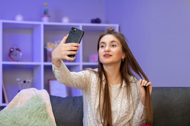 現代のスマートフォンの波手こんにちはを保持している幸せな若い女性ブロガーインフルエンサー。携帯を見て笑顔のvloggerの女の子がビデオ通話をし、vlogを撮影して自分撮りをする