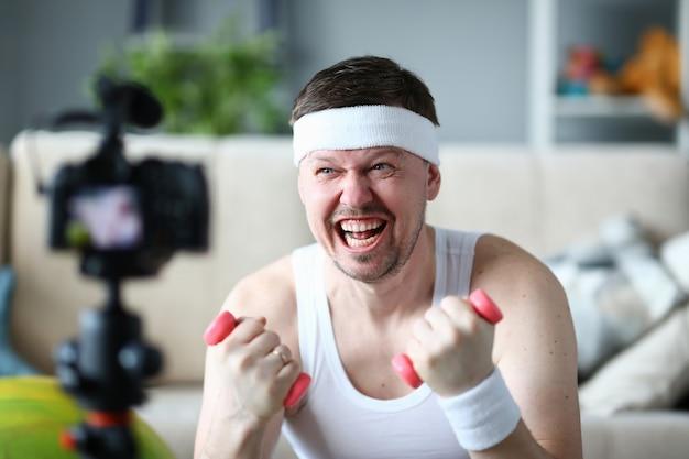 ダンベルを手に持って幸せそうな顔を持つvlogger