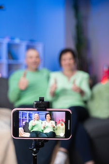 オンラインの視聴者にチャンネルを高く評価してチャンネル登録するように依頼するvlogger。幸せな笑顔の年配のカップルと孫娘のカメラでビデオメッセージを自宅で記録します。
