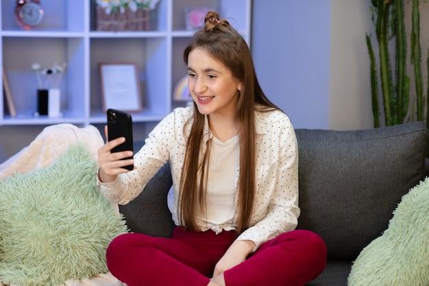 Счастливый влияние блоггера молодой женщины держа современную умную руку волны телефона здравствуйте! улыбающаяся девушка vlogger, глядя на мобильный телефон, делает видеозвонок, снимает влог, принимая селфи на фоне дома
