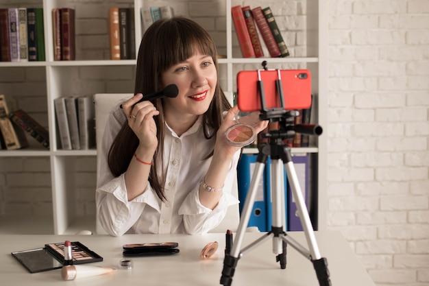 化粧品を示す美容女性vlogger