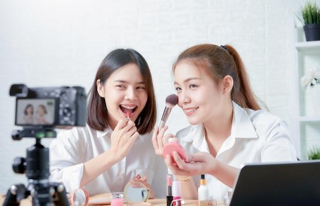 Две азиатские женщины красоты vlogger онлайн видео показывает макияж на косметические продукты и видео в прямом эфире