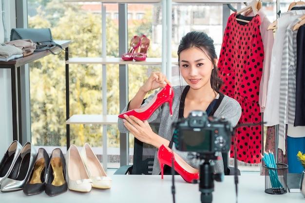 Молодая азиатская дружелюбная девушка в прямом эфире видеоблог (vlogger) и распродажа обуви в интернет-магазине.