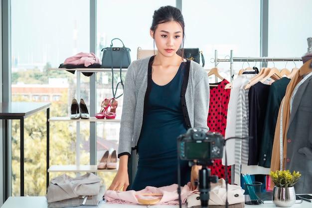 Молодая азия счастливая дама в прямом эфире видеоблог (vlogger) и распродажи одежды в интернет-магазине.