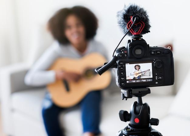 Женский vlogger записывает музыку, связанную с вещанием дома
