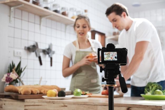 キッチンルームで料理をしている幸せな白人カップルのビデオブログ、写真家やビデオとライブストリーミングのコンセプト、vlogger、ブロガーのカメラのプロのデジタルミラーレスカメラ録画ビデオブログ。