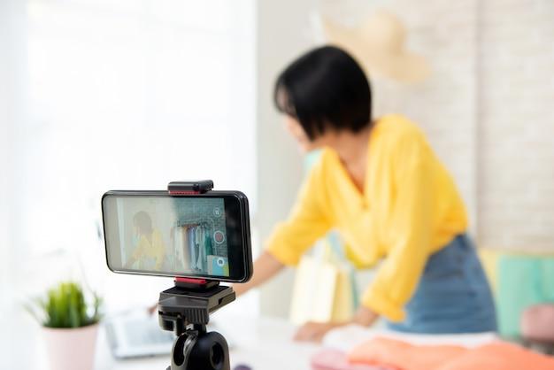 若い女性のファッションvloggerライブストリーミングビデオを携帯電話で